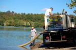 Joel Morrow helping fish commission to empty truck of remaining muskies.